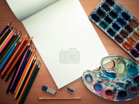 Photo pour Photo d'outils de bureau, crayons de couleur et aquarelle sur la table - image libre de droit