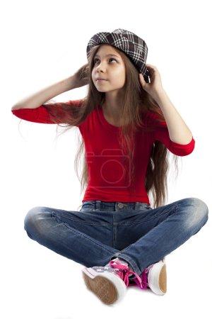 Foto de Hermosa chica adolescente en sombrero sentado sobre fondo blanco - Imagen libre de derechos