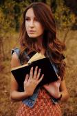 Cute young woman in the autumn forest reading a book