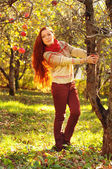 Young redheaded woman with long straight hair in the apple garde
