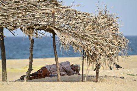 Old man resting in shadow in Sri Lanka beach