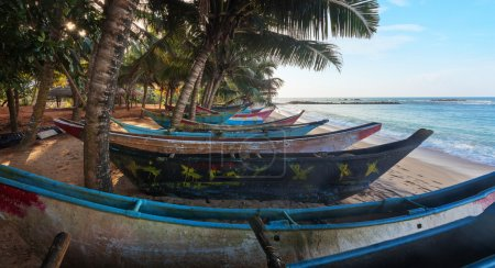 Tropical beach with palms and fishing boats