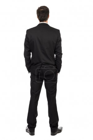 Full body portrait of young businessman, back view, with hands i