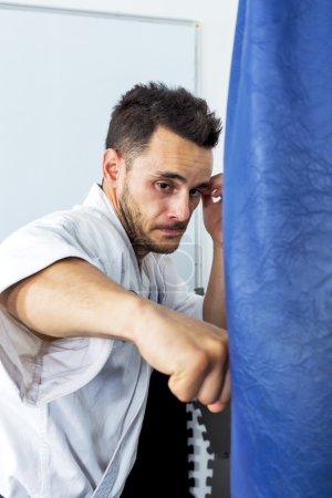 Photo pour Jeune homme en jetant des coups de poing à un lourd sac de boxe au cours de sa formation de kimono - image libre de droit