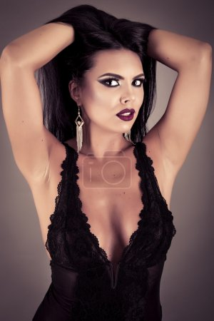 Closeup portrait of a sensual brunette woman posing in sexy blac