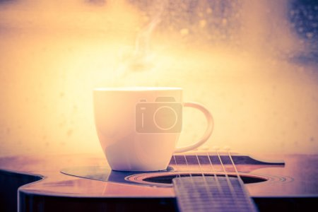Coffee cup and acoustic guitar next the window with drop water