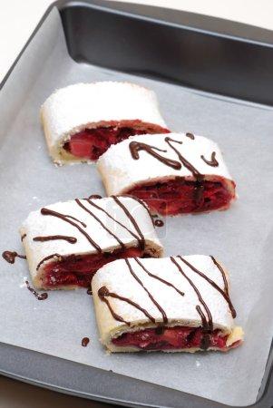 Photo pour Rouleaux suisses aux cerises et fraises décorés de chocolat sur parchemin - image libre de droit