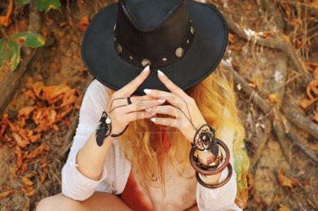 Photo pour Belles mains féminines avec bracelets dreamcatcher chic boho et chapeau en cuir noir, manucure blanche, sans visage, style indépendant, automne en plein air - image libre de droit