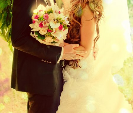 Photo for Sunny bride and groom embracing with bouquet of flowers. - Royalty Free Image