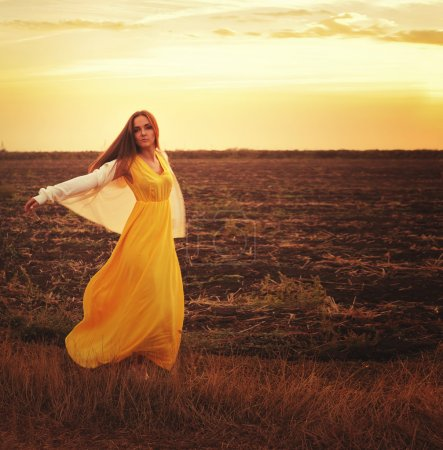 Fashion woman dressed in long yellow dress and white jersey walking on a sunset field.