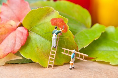 Little people paint leaf on autumn colors. The concept of teamwo