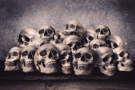 Stacked human skulls on old wooden table in front ...