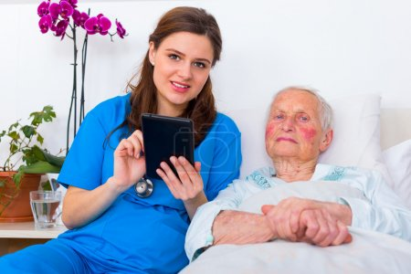 Photo for Caring doctor helping a senior patient to use a digital tablet. - Royalty Free Image
