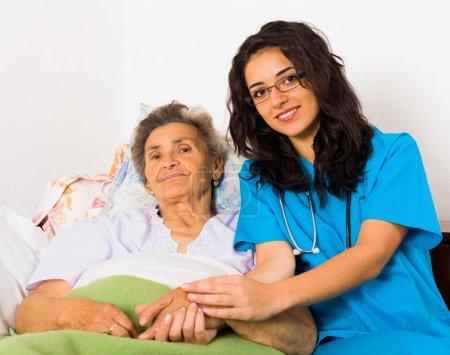 Photo pour Joyeuses infirmières joyeuses prenant soin de patients âgés aimables aidant leurs jours dans une maison de soins infirmiers . - image libre de droit