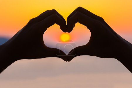 Photo for Female hands making a heart shape in the sunset - health, love concept. - Royalty Free Image