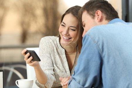 Photo pour Heureux couple occasionnel rire et regarder ensemble le streaming de vidéos en ligne dans un téléphone intelligent générique rencontres dans un bar avec un coucher de soleil chaud en plein air dans le fond - image libre de droit