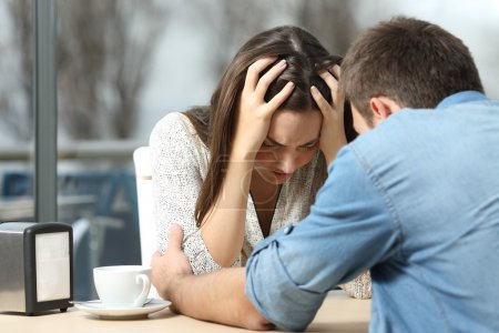 Photo for Male comforting to a sad depressed female who needs help in a coffee shop. Break up or best friend concept - Royalty Free Image