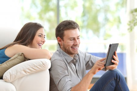 Cheerful couple using a tablet at home