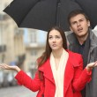 Постер, плакат: Couple annoyed in a rainy day