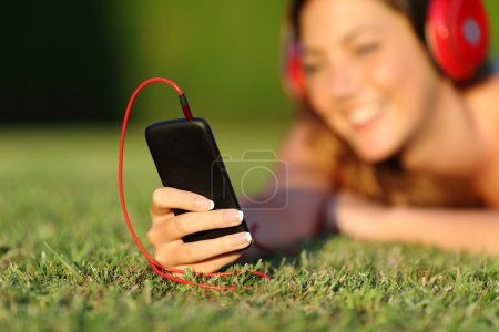 Close up of a woman with headphones holding a smart phone