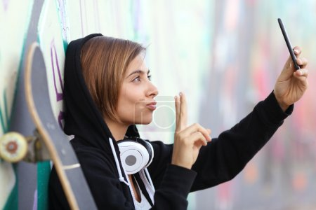 Photo for Skater teenager girl taking a photograph with smart phone camera with blurred graffiti wall in the background - Royalty Free Image