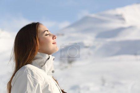 Photo pour Profil d'une femme de l'Explorateur, respirer l'air frais en hiver avec une montagne enneigée dans le fond - image libre de droit