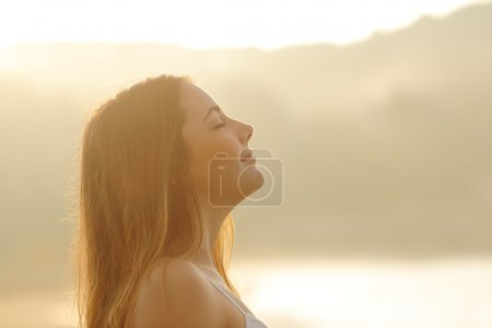 Woman breathing deep fresh air in the morning sunrise