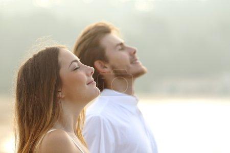 Photo pour Profil d'un couple d'homme et femme, respirer l'air frais profond ensemble au coucher du soleil - image libre de droit