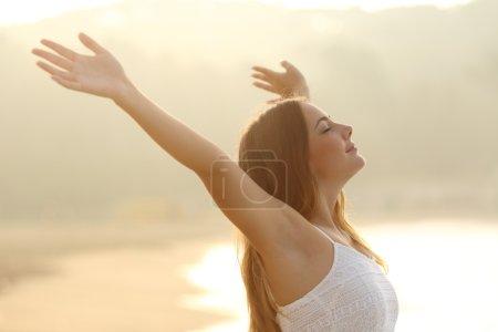 Photo pour Femme détendue respirant de l'air frais levant les bras au lever du soleil avec un fond doré chaleureux - image libre de droit