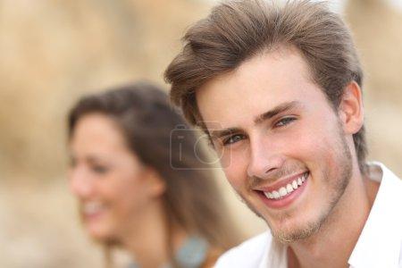 Photo pour Bel homme Gros plan portrait avec une dent blanche parfaite et sourire avec une fille en arrière-plan - image libre de droit