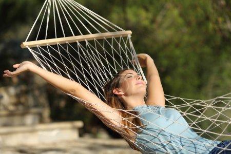 Photo pour Femme heureuse détente sur un hamac en vacances et en levant les bras dans la montagne - image libre de droit