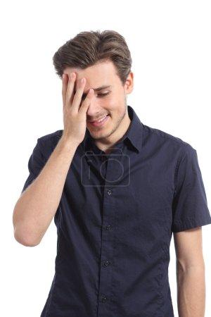 Foto de Hombre avergonzado sonriendo cubriendo su rostro con una mano aislada sobre un fondo blanco - Imagen libre de derechos