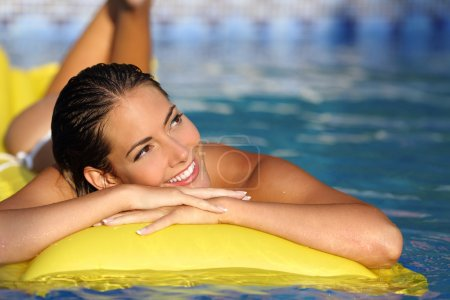 Girl enjoying summer vacations on a mattress in a pool and looking at side