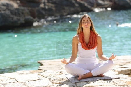 Relaxed girl doing yoga exercises on holidays in a...