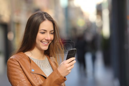 Photo for Happy woman using a smart phone in the street with an unfocused background - Royalty Free Image