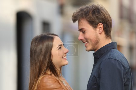 Profile of a couple looking each other in the street