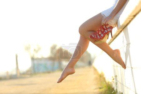 Photo pour Silhouette de jambes de femme avec des talons hauts suspendus de sa main et assis sur un mur - image libre de droit