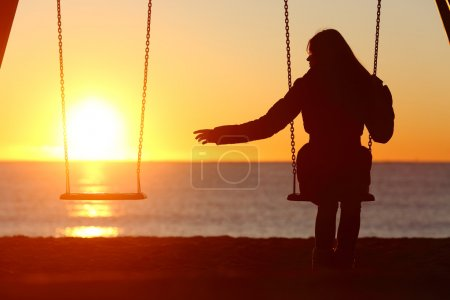 Photo for Single or divorced woman alone missing a boyfriend while swinging on the beach at sunset - Royalty Free Image