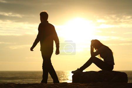 Photo pour Silhouette de couple brisant une relation sur la plage au coucher du soleil - image libre de droit