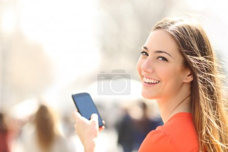 Photo for Happy woman smiling and walking in the street using a smartphone and looking at camera - Royalty Free Image