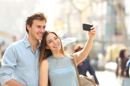 Photo for Happy couple of tourists photographing a selfie in a city street in a sunny day - Royalty Free Image
