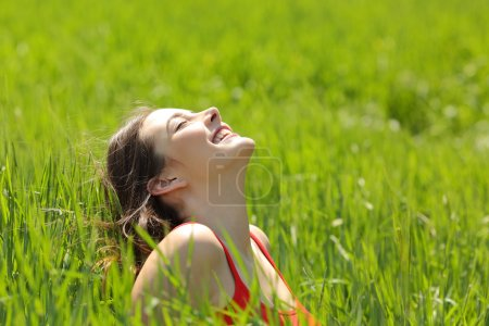 Photo for Happy girl face breathing fresh air and enjoying the sun in a meadow in a summer sunny day - Royalty Free Image