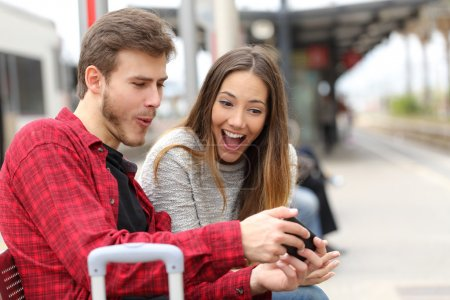 Photo for Funny couple playing games with a smart phone in a train station while they are waiting - Royalty Free Image