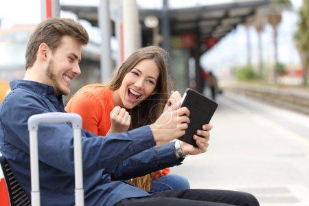 Photo pour Couple euphorique regardant des films ou jouant à des jeux sur une tablette dans une gare - image libre de droit