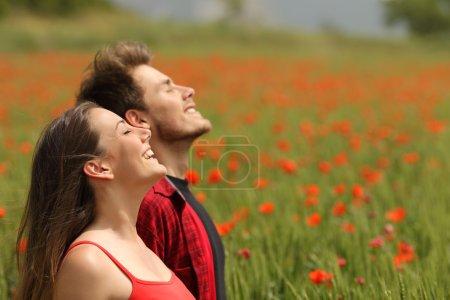 Photo pour Couple heureux, respirant l'air frais dans un champ coloré avec des fleurs de pavot rouge - image libre de droit