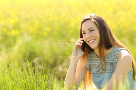 Woman calling on the mobile phone in a green field