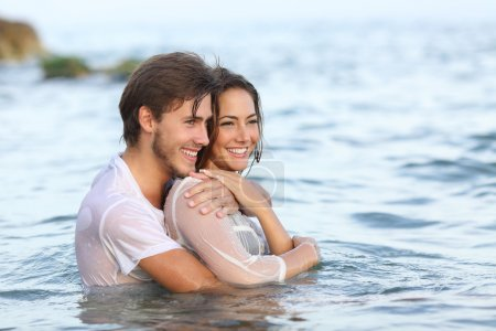 Photo pour Happy couple in love hugging and bathing on the beach and looking away - image libre de droit