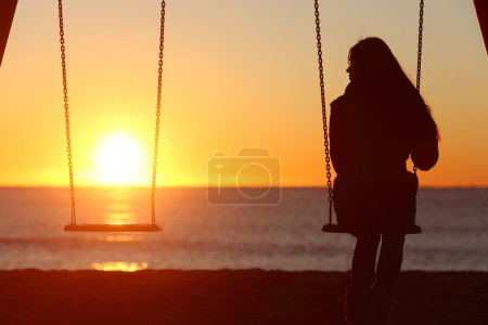 Photo for Single woman alone swinging on the beach and looking the other seat missing a boyfriend - Royalty Free Image