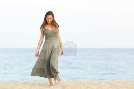 Candid dreamer girl walking on the sand of the beach