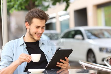Photo for Happy man reading an ebook or tablet in a coffee shop terrace holding a cup of tea - Royalty Free Image